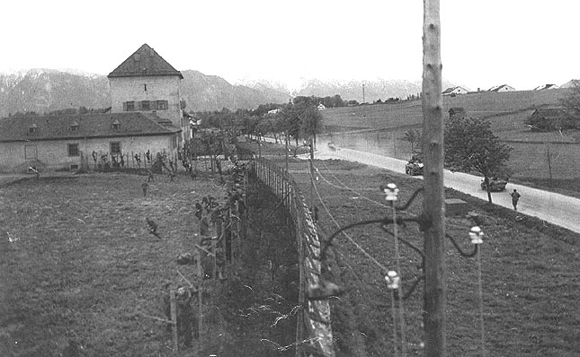 A firefight erupts outside of the Murnau POW camp between American and Nazi soldiers. Prisoners in the camp are seen running towards or away from the barbed wire fence. April 29, 1945